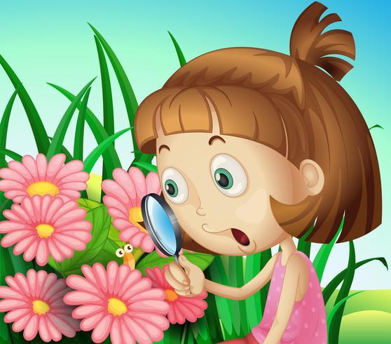 Een meisje met een vergrootglas in de tuin