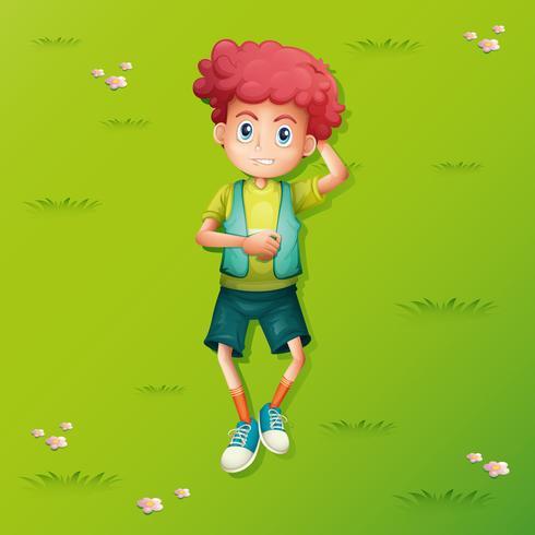 Netter Junge, der auf Gras liegt
