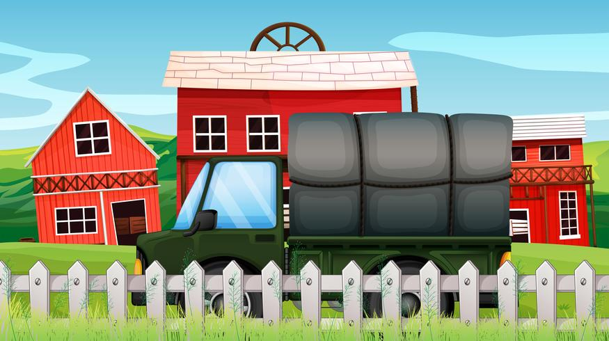 Un cargamento verde frente a un granero dentro de la cerca.