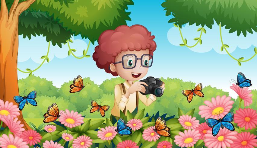 Pojke tar bild av fjärilar i trädgården vektor
