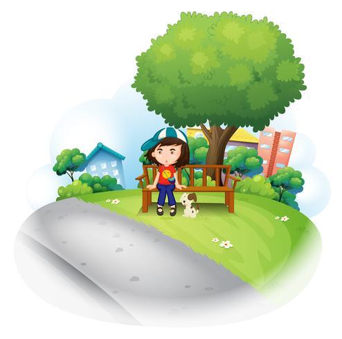 En tjej som sitter vid träbänken nära det stora trädet