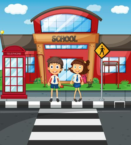 Två studenter korsar vägen framför skolan