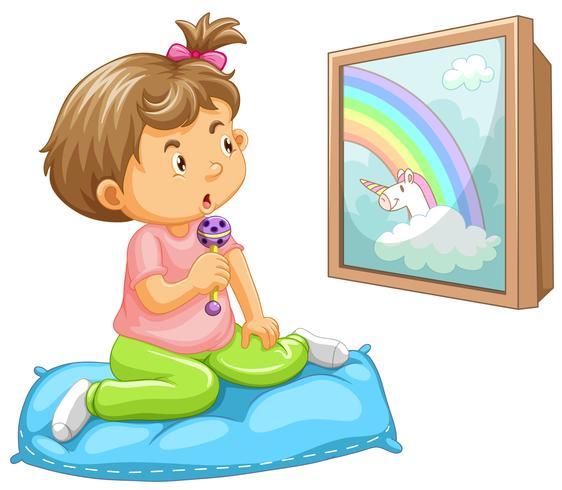 Bambino della ragazza che esamina unicorno
