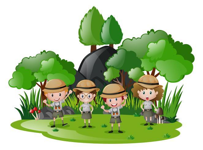 Cuatro niños en traje de safari divirtiéndose en el bosque