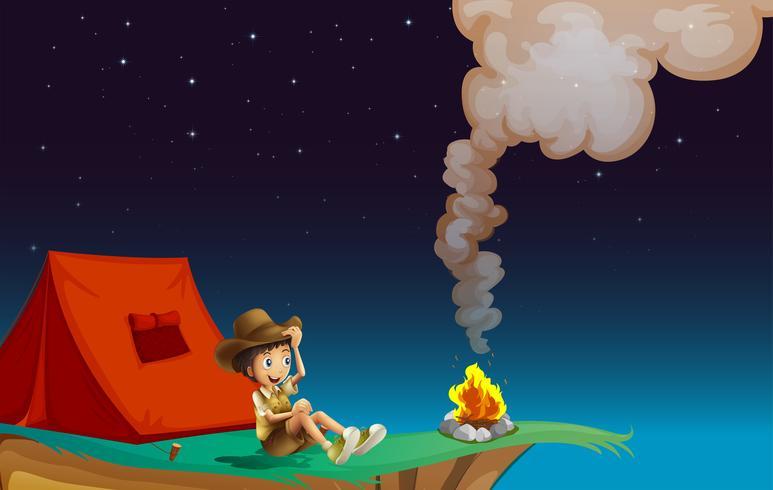 Un boy scout acampando cerca del acantilado.