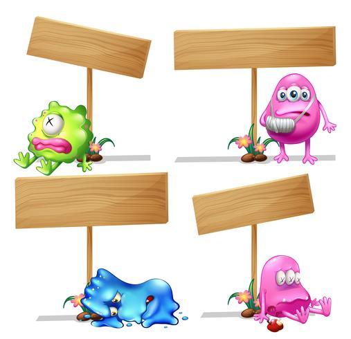 Quattro segni di legno con mostri carini