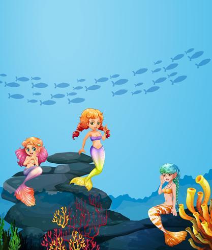 Three mermaids swimming under the ocean