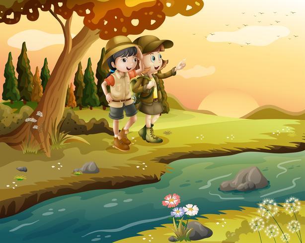 Una niña y un niño a la orilla del río.