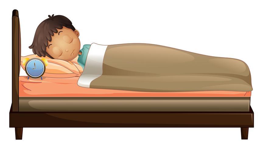 Ein Junge, der mit einem Wecker schläft