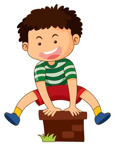 Il ragazzo felice che salta sopra il mattone