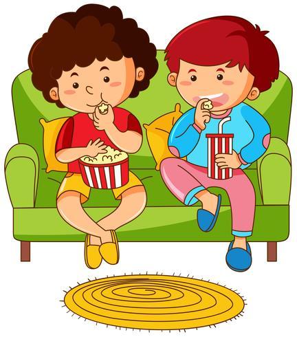 Due ragazzi che mangiano popcorn sul divano