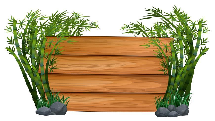 Planche de bois avec des bambous en arrière-plan