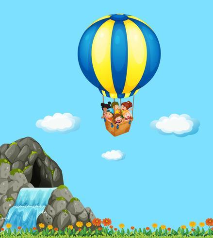 Niños montados en globo en el cielo.