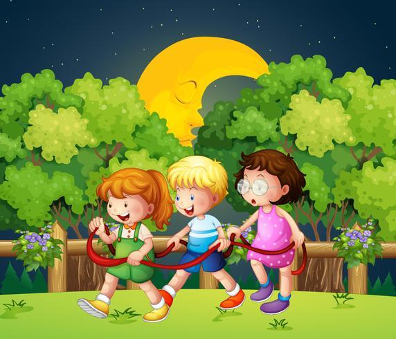 Três crianças andando ao ar livre no meio da noite