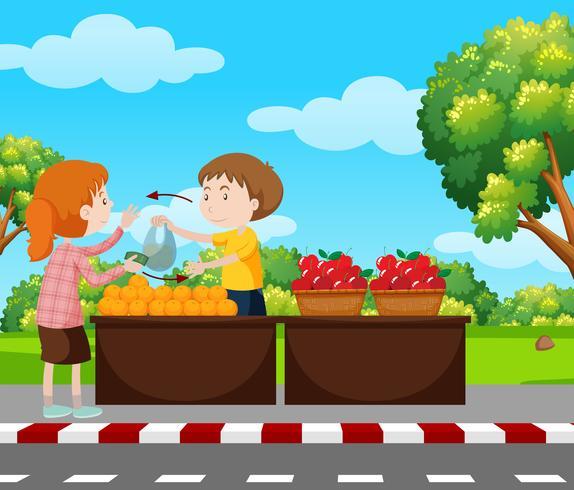 Junge, der Früchte auf Pflasterung verkauft