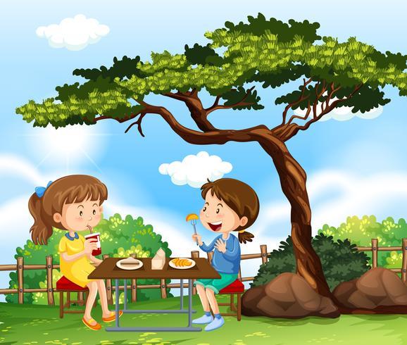 Twee meisjes die picknick in park hebben