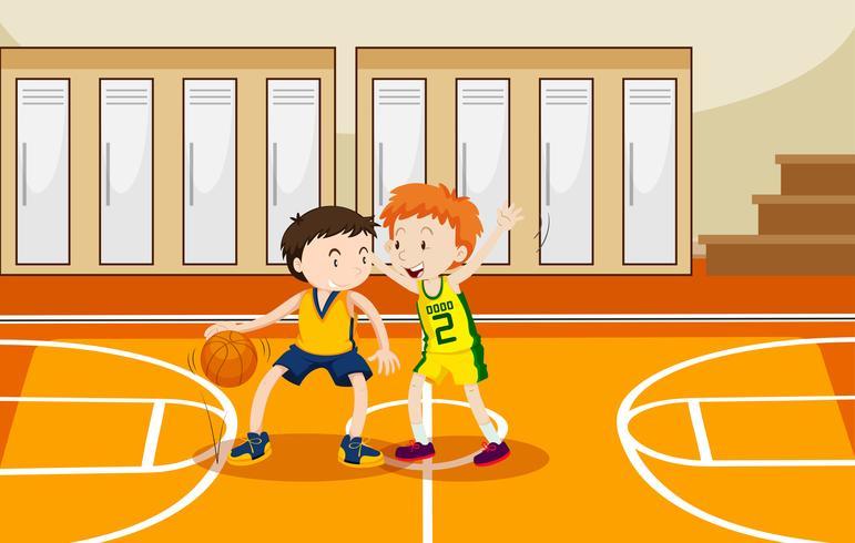 Zwei Jungen, die Basketball in der Turnhalle spielen