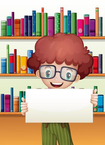 En pojke som håller en tom kartong som står framför bokhyllorna