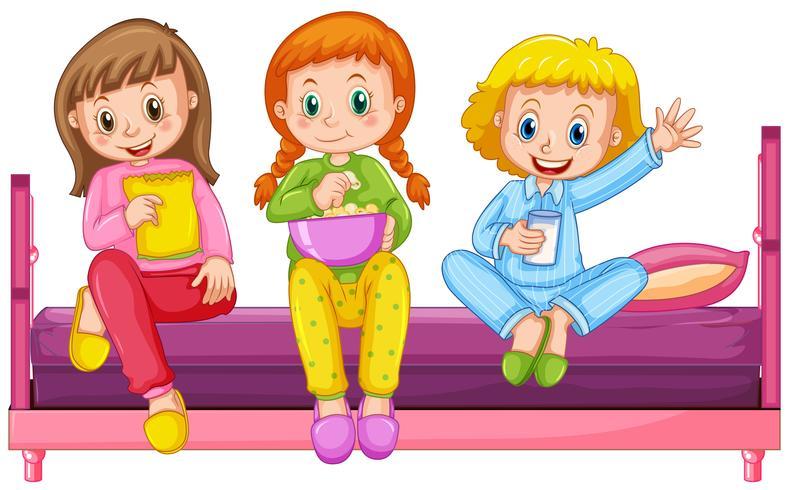 Tre flickor pyjamas sitter på sängen
