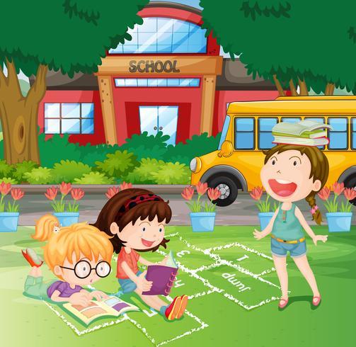 Filles lisant dans la cour d'école