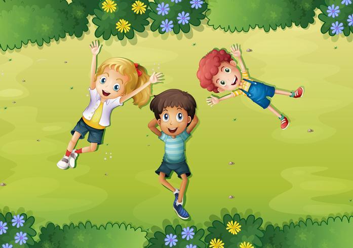 Tres niños felices en la hierba verde vector