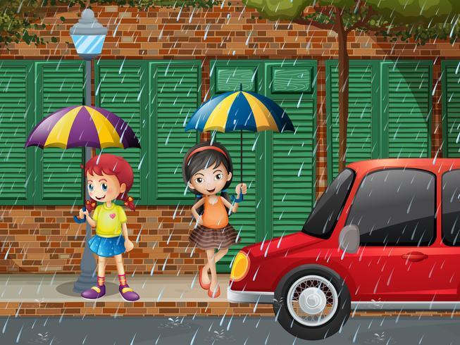 Due ragazze in piedi sul marciapiede sotto la pioggia