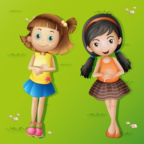 Två tjejer ligger på grönt gräs