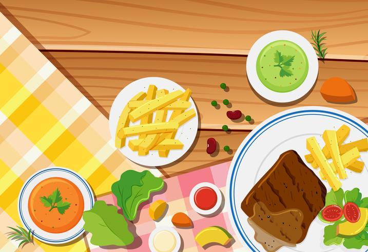 Scène de table avec des frites et un steak sur le plat