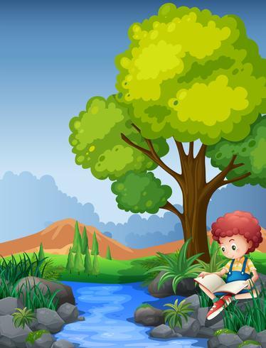 Liten pojke läser bok vid floden