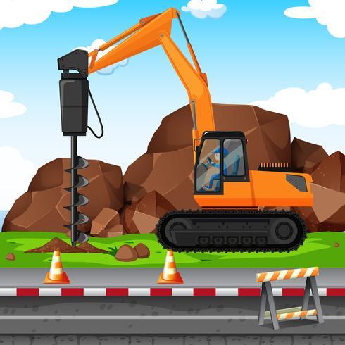 Hombre cavando hoyo con taladro en el sitio de construcción