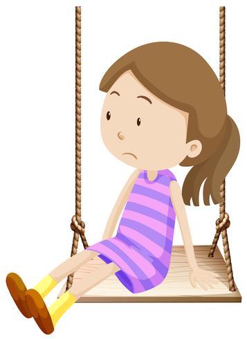 Bambina su altalena in legno