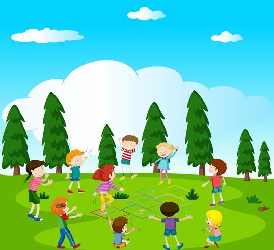 Lyckliga barn spelar hopscotch i parken