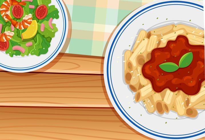Pasta en salade op een houten bord