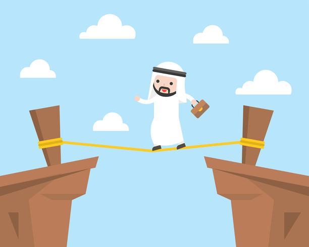 Uomo d'affari arabo che cammina sulla corda attraverso la scogliera, concetto della gestione dei rischi