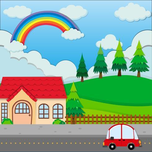Röd bil på vägen och ett hus