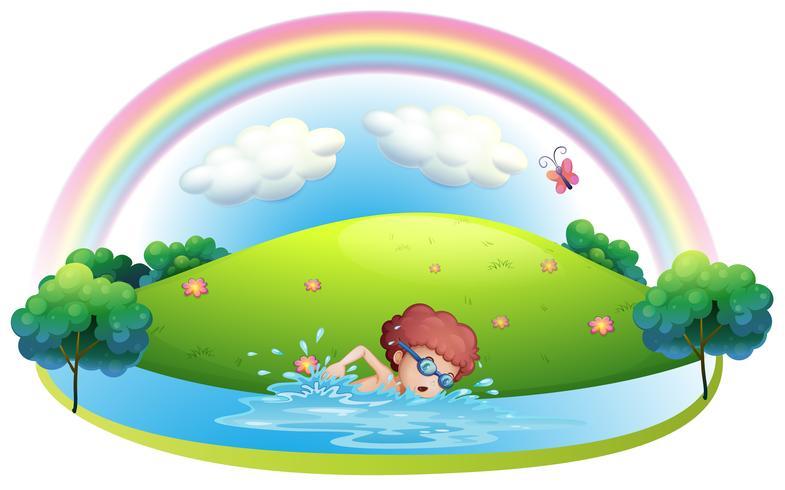 Ein junger Mann, der nahe dem Hügel mit einem Regenbogen schwimmt