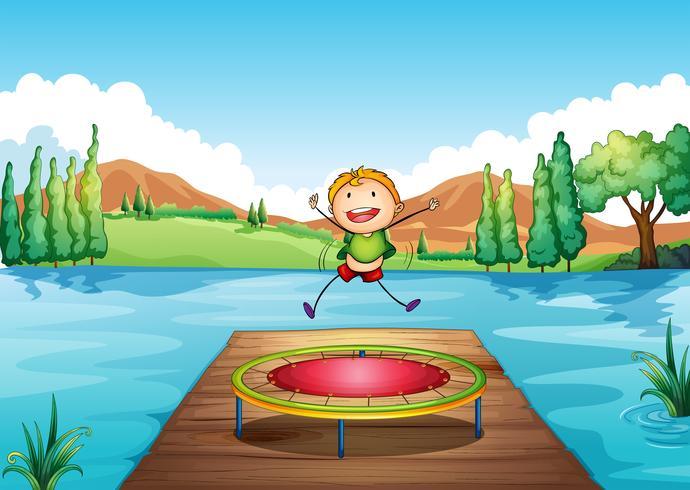 Een jongen die met de trampoline speelt bij de rivier