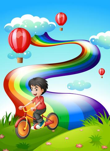 A boy biking at the hilltop with a rainbow vector