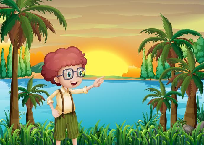 En ung pojke som pekar på träden