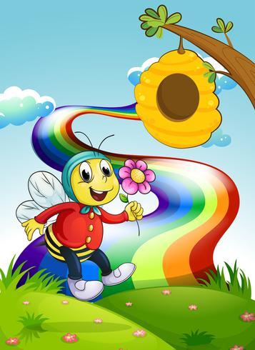 Una abeja sonriente sosteniendo una flor en la cima de la colina con un arco iris