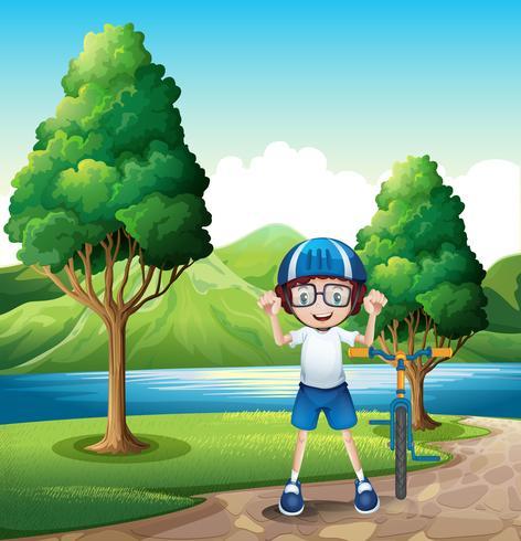 Un giovane ragazzo e la sua bici giocattolo in piedi vicino agli alberi nella riva del fiume