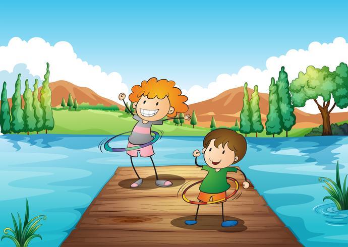 Dos niños jugando al hulahoop en el río