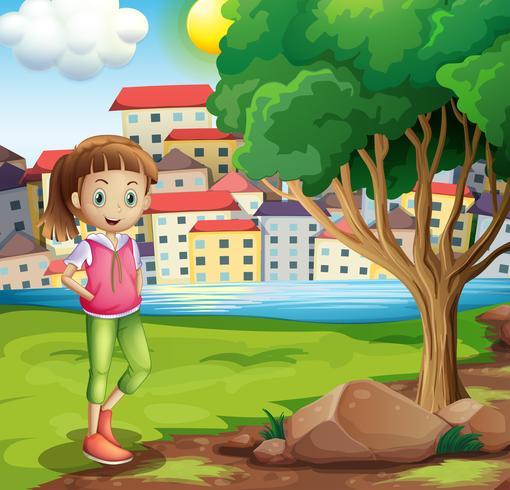 Una ragazza sulla sponda del fiume vicino all'albero