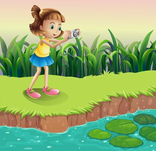 Una niña tomando fotos en el estanque.