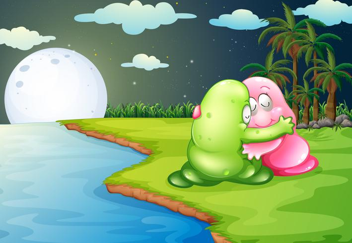 A green monster comforting the pink monster at the riverbank