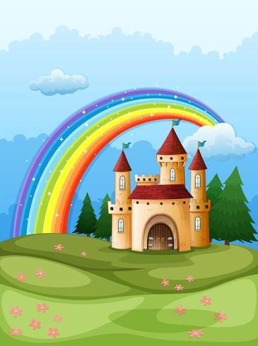 Un château au sommet d'une colline avec un arc en ciel