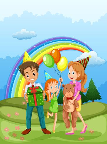 Una familia feliz en la cima de la colina y un arco iris en el cielo.