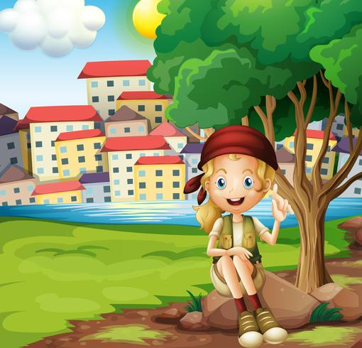 A girl sitting above the rock under the tree