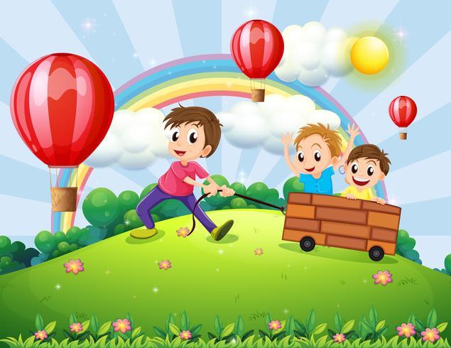 Tre ragazzi che giocano in cima alla collina con un arcobaleno e palloncini galleggianti