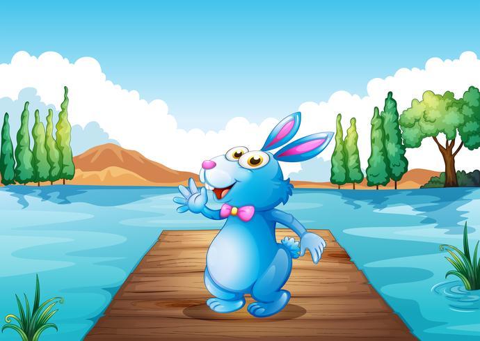 Een konijntje boven de houten brug bij de rivier